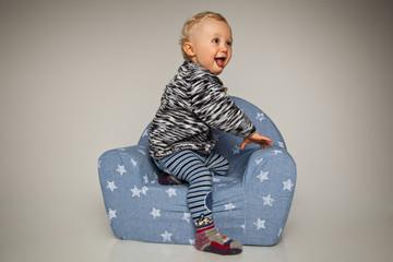 Baby spielt mit seinem Sessel