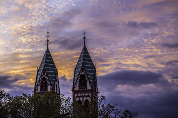 Wundervoller Sonnenuntergang in Freiburg über einer Kirche nahe des Bahnhofes an einem Herbstabend