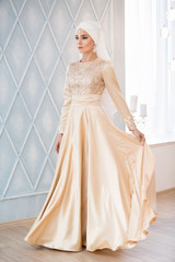 Portrait of a beautiful muslim bride in gold wedding dress with Beautiful white headdress