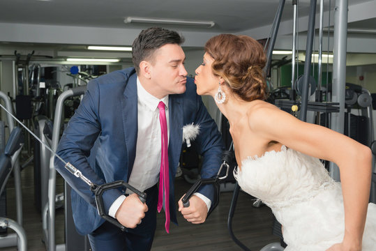 Bride and groom kissing in gym