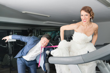 Bride and groom in the gym. Bride on treadmill pulling groom for tie