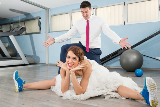 Bride and groom in the gym. Bride streching and groom standing under her