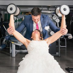 Bride and groom in the gym. Groom helping bride with weights