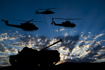 Military tank and helicopters silhouetted against dawn or dusk blue sky