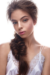 Beautiful girl in image of bride with plait. Model with nude makeup and silk underwear. Beauty face. Photo was taken in a studio.