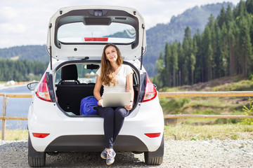 Young woman using her laptop sitting in car trunk