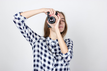 Portrait of a pretty woman  in plaid shirt making photo standing over gray background
