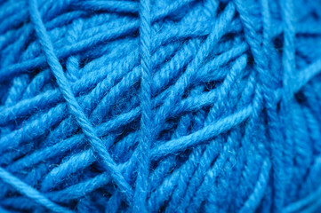 Woolen yarn ball, skein of tangled blue sewing threads, selective focus