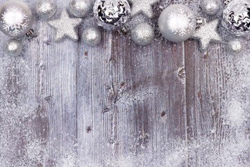 Silver Christmas ornament top border with snow frame on a rustic wood background