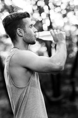 Young athlete drinking water in park.black and white photo