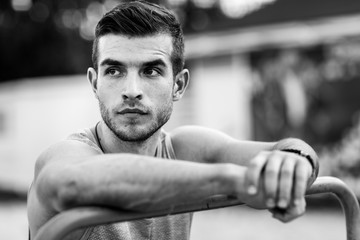 Black and white portrait of sporty man relaxing after training