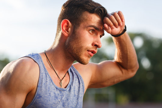 Young muscular sweaty man after workout outside on sunny day