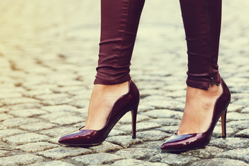 Woman wearing classic high heel toe shoes. Model posing on the street. Elegant outfit. Female fashion concept. Close up. Toned