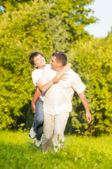 Happy Caucasian Family of Father and Son Piggybacking Outdoors.