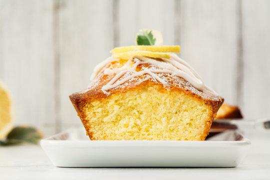 Lemon loaf with white glaze on wooden background