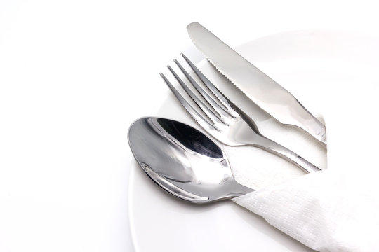 Knife, spoon and fork with serviette over dish, isolated on the white background with copy space for text.