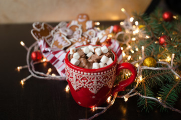Red mugs with hot chocolate and marshmallows and gingerbread cookies. Christmas holiday concept
