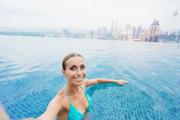 Vacation and technology. Pretty young woman taking selfie while swimming in roof top pool with beautiful city view.