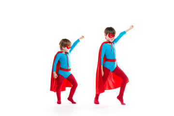 Boys is dressed up as a superhero and pointing up with a mask and cloak.