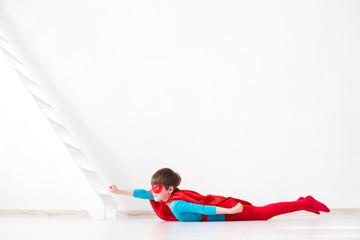 Kid as Superman dressed in flight position.