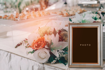 vintage blank frame and flowers on table in wedding day