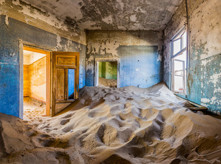 Room full of sand with colored door in the ghost town of Kolmanskop, Namibia Wall mural