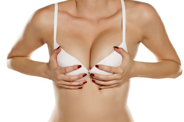 woman in a white bra holding her breasts with her hands