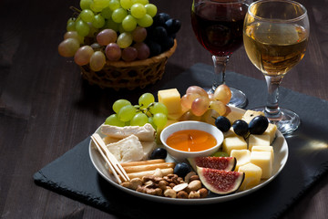 Plate with deli snacks and wine on a dark background