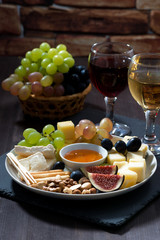 Plate with deli snacks and wine, vertical