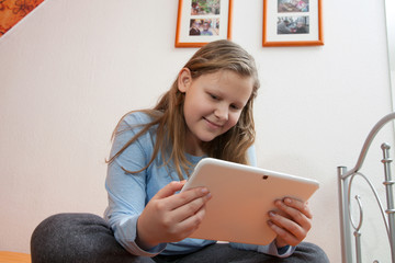 teenegar girl sitting on bed and watching video on tablet
