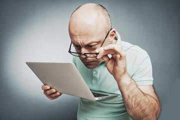 Closeup portrait surprised man working on laptop computer lookin