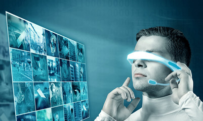 Young man in futuristic glasses. Projection of multimedia images. Future technology concept.