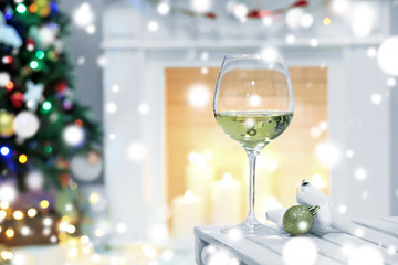 Glass of white wine on blurred Christmas interior background. Christmas celebration concept.