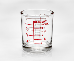 Measuring glass on white background. Medical equipment. Shot glass. Selective focus.