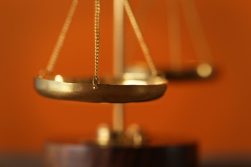 Justice scales on blurred orange background, closeup