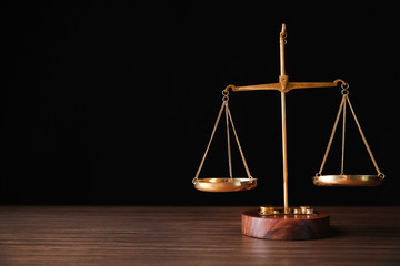 Justice scales on wooden table and  black background
