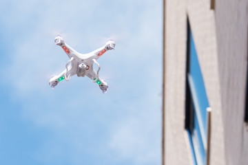 Aerial quadcopter drone with camera flying near a buildings window