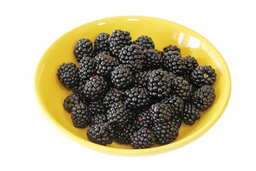 Juicy shiny blackberries in a bright yellow plate on white background