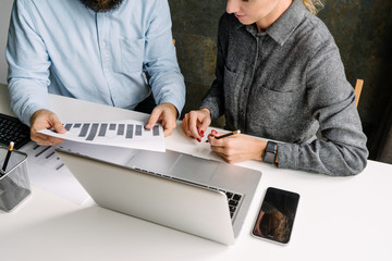 Business people sitting at white desk and discussing. Man holding in hands documents. Woman holding black pencil and taking notes. Teamwork. On table laptop, graphics, pencil holders, smartphone.