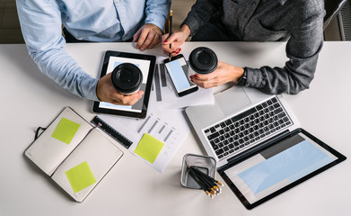 View from above. Business piople sitting at a white desk, holding cups of coffee and talking.Teamwork. On table laptop with blue screen, smartphone, digital tablet, graphics, notebook, pencil holders.