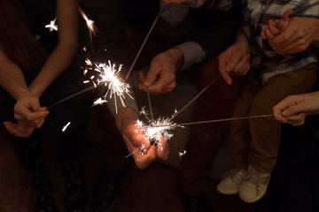 hands of a few people are holding sparklers,blurry