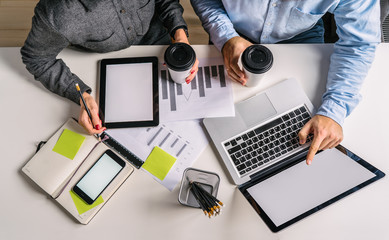 View from above.Business people sitting at desk. Businessman pointing at laptop screen,holding in his other hand cup of coffee.Teamwork.On table smartphone,digital tablet, graphics, notebook,pencils.