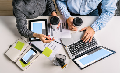 View from above. Businesswoman showing pencil on screen of laptop and holding cup of coffee.Businessman printing on laptop.Teamwork.On table smartphone,digital tablet, graphics,notebook,pencil holders
