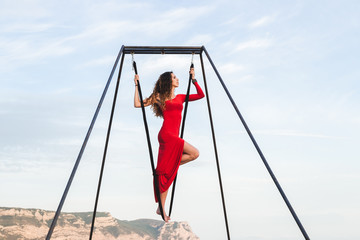 Woman in red dress practicing fly-dance poses in a hammock outdo