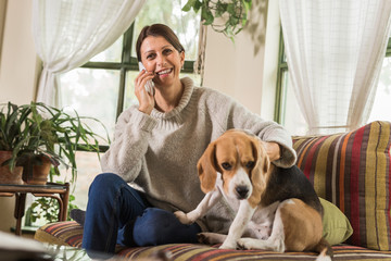 Woman using her smart phone while playing with  dog in home