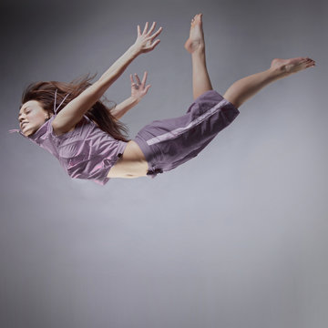 girl flying, jump and coast, on gray background
