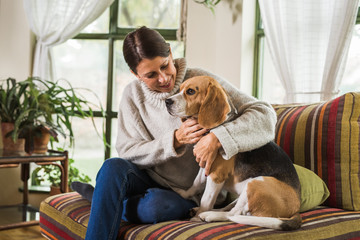 woman enjoying a cuddle with her dog at home