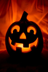 Spooky Halloween Jack-o-Lantern glowing on a bright orange background with mysterious shadows
