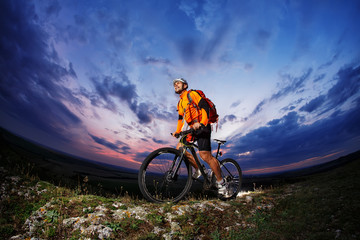 Man in helmet stay on bicycle under sky with clouds.