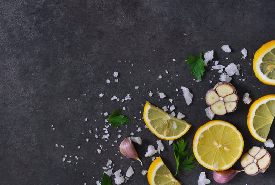 Black food background with slices of lemon, salt and garlic with copy space, top view